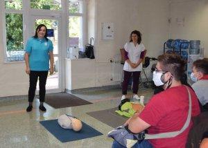 Osoba stojąca przy manekinie do udzielania pierwszej pomocy