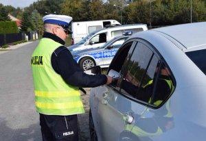 Policjant stojący przy samochodzie