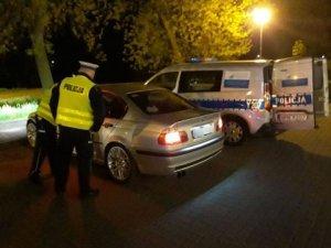 Policjanci stoją przy kontrolowanym samochodzie