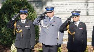 Policjant w umundurowaniu galowym i komendanci straży oddają honor
