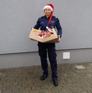 Policjantka z darami dla potrzebujących w mundurze i czapce św. Mikołaja