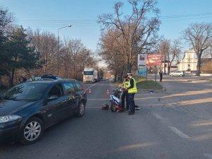 Zdjęcie przedstawia na pierwszym planie fragment pojazdu osobowego biorącego udział w zdarzeniu drogowym. Po prawej stronie stoi dwóch policjantów i wykonuje oględziny uszkodzonego motocykla. W dali widać stojące samochody.