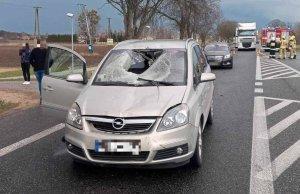 Zdjęcie przedstawia srebrny samochód osobowy, który ma uszkodzoną maskę, szybę i dach. Auto ma otwarte drzwi od strony pasażera. Za drzwiami stoją dwie osoby. Za uszkodzonym pojazdem stoją inne pojazdy.