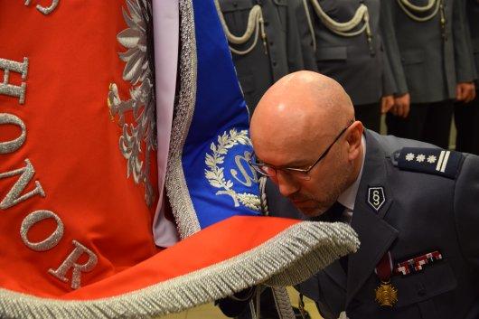 Insp. Arkadiusz Zgieb żegna się ze sztandarem Komendy Powiatowej Policji w Żyrardowie klęcząc na kolanie i całując płat sztandaru