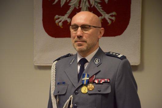insp. Arkadiusz Zgieb w tle godło Polski
