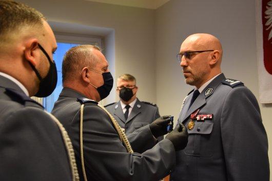 mł.insp. Dariusz Brzezicki przypina medal na marynarce Komendanta Powiatowego Policji  Żyrardowie